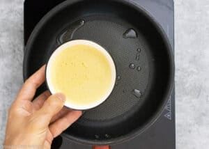 Adding chickpea socca flatbread batter to the frying pan to cook