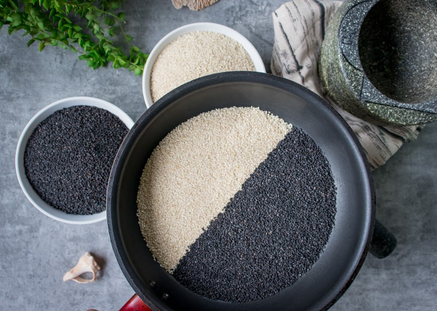 black and white sesame seeds in a frying pan ready to toast