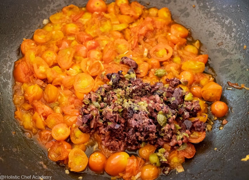 adding the capers and olives to tomato sauce for puttanesco
