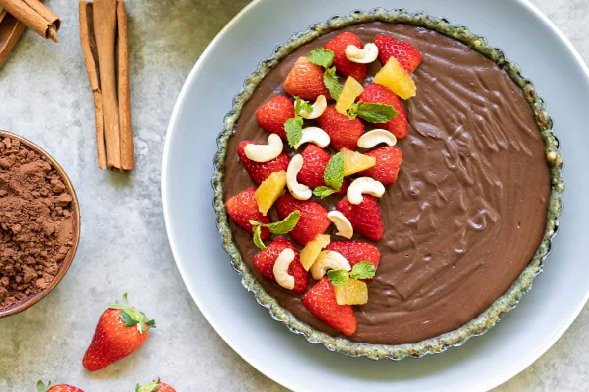 raw cheesecake garnished with fresh strawberries, orange, cashew and mint leaf