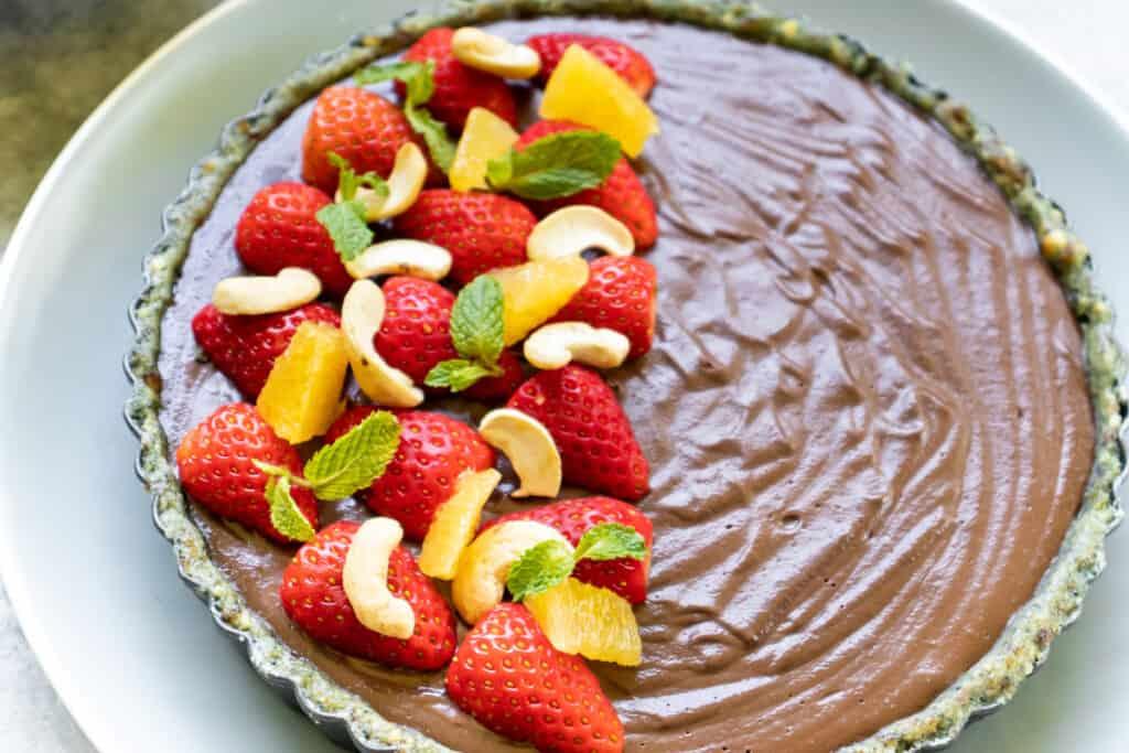 chocolate cheesecake garnished with orange, strawberry, cashew and mint