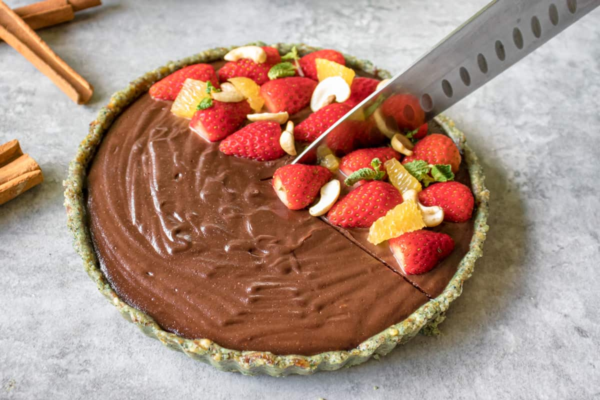 slicing the raw vegan cheesecake before serving