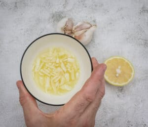 soaking slice garlic in lemon juice for making the perfect hummus