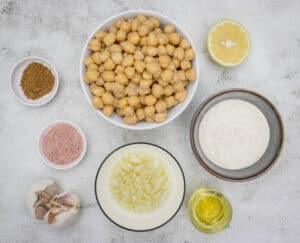 Add the chickpeas, salt, cumin, garlic, lemon juice, olive oil to a high speed blender.