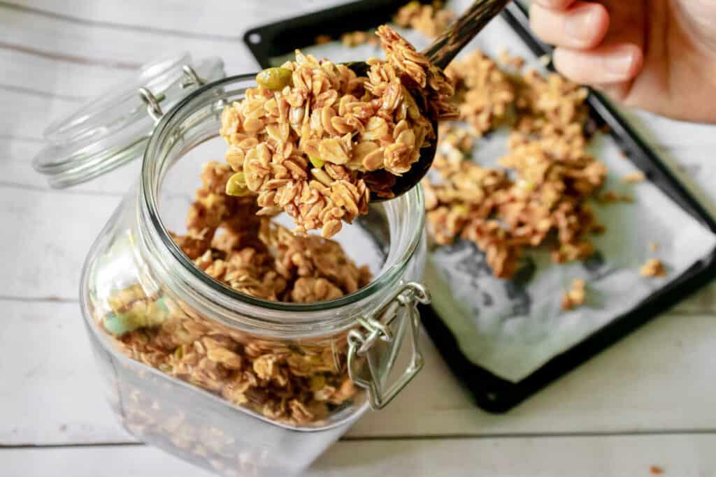 adding-vegan-granola-to-a-glass-jar